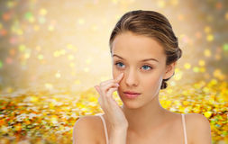 Young woman applying cream to her face Stock Images