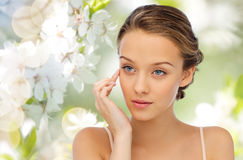 Young woman applying cream to her face Royalty Free Stock Image