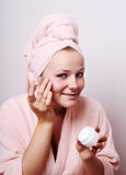 Young woman applying creme. On face Royalty Free Stock Images