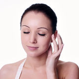 Young woman applying creme on face Stock Image