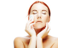 Young woman applying a creme on her face Stock Photo