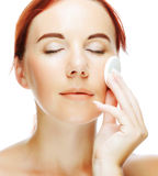 Young woman applying a creme on her face Stock Photography