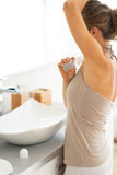Young woman applying deodorant on underarm Stock Images