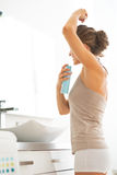 Young woman applying deodorant on underarm Royalty Free Stock Photos