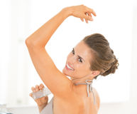 Young woman applying deodorant on underarm Royalty Free Stock Images