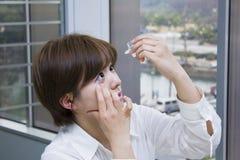 Young woman applying eye drops. Young businesswoman applying eye drops stock image