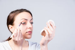 Young woman applying eye makeup Stock Photo