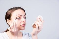 Young woman applying eye makeup Stock Photo