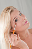 Young woman applying eye shadow with a brush Stock Images