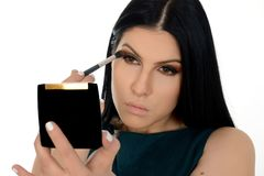 Young woman applying eye shadow powder, holding small mirror stock photo