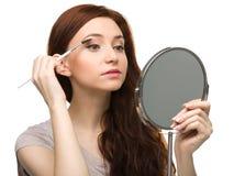 Young woman is applying eyeshadow Stock Image
