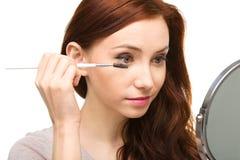 Young woman is applying eyeshadow Stock Photo