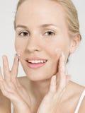 Young Woman Applying Facial Cream royalty free stock photo