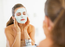 Young woman applying facial mask in bathroom Royalty Free Stock Photo