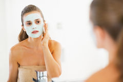 Young woman applying facial mask in bathroom Royalty Free Stock Photography