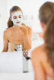 Young woman applying facial mask in bathroom Stock Photography