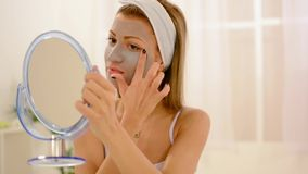 Young Woman Applying Facial Mask stock footage