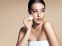 Young woman applying foundation on face with powder puff, skin care concept Royalty Free Stock Image