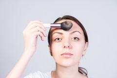 Young Woman Applying Foundation Makeup on Forehead Royalty Free Stock Photo