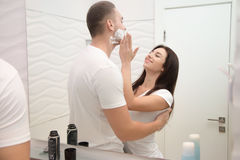 Young woman applying gently foam for a man to shave stock image