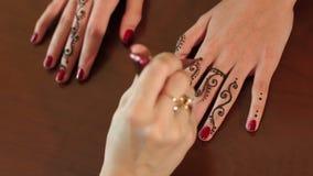 Artist applying henna tattoo on bride`s hands. 4K