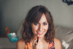 Young woman applying her lipstick Stock Images
