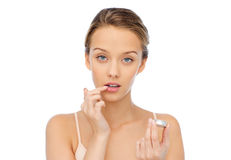Young woman applying lip balm to her lips Royalty Free Stock Image