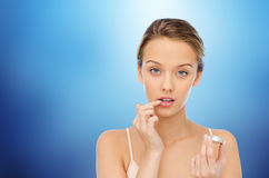 Young woman applying lip balm to her lips Stock Photo