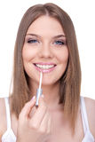 Young woman applying lip gloss Stock Photography