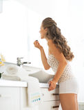 Young woman applying lip gloss in bathroom Royalty Free Stock Images