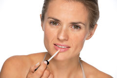 Young woman applying lip gloss Royalty Free Stock Photos