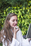 A  young woman applying a lipstic Royalty Free Stock Image