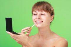 Young woman applying lipstick Stock Image