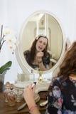 Young woman applying lipstick. Young women applying lipstick Stock Image