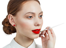 Young woman applying lipstick with an applicator. Isolated on white Royalty Free Stock Photography