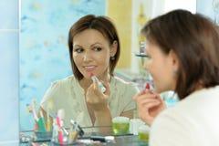 Young woman applying lipstick. Beautiful young woman applying lipstick in front of mirror Stock Image