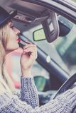 Young woman applying lipstick in car. Young attractive woman looking in rear view mirror painting her lips doing applying make up while driving the car Royalty Free Stock Photo