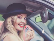 Young woman applying lipstick in car. Young attractive woman looking in rear view mirror painting her lips doing applying make up while driving the car Stock Photo