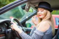 Young woman applying lipstick in car. Young attractive woman looking in rear view mirror painting her lips doing applying make up while driving the car Stock Image