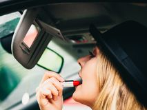 Young woman applying lipstick in car. Young attractive woman looking in rear view mirror painting her lips doing applying make up while driving the car Stock Photography