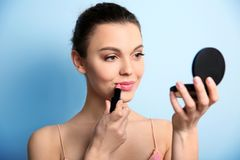 Young woman applying lipstick. On color background. Professional makeup products Stock Images