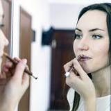 Young woman applying lipstick in front of a mirror in office. Correction of the shape of the lips Stock Photo