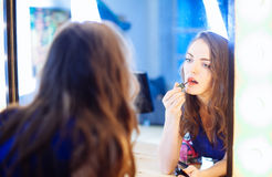 Young woman applying lipstick in front of a mirror Stock Photography