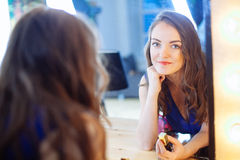 Young woman applying lipstick in front of a mirror Royalty Free Stock Photography