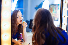 Young woman applying lipstick in front of a mirror. In studio Stock Image