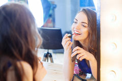 Young woman applying lipstick in front of a mirror. In studio Stock Photography