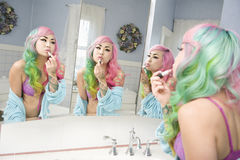 Young woman applying lipstick on her lips with multiple mirror reflections Stock Images