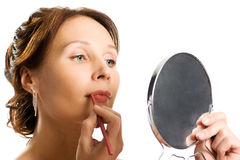Young woman applying lipstick looking at mirror Royalty Free Stock Photography