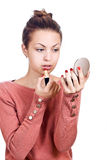Young woman applying lipstick. Looking at mirror Royalty Free Stock Image
