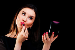 Young woman applying lipstick looking at mirror. On black Stock Images